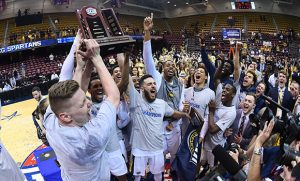 Men's basketball team celebrating with trophy on court