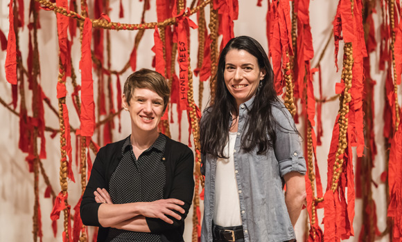 Two professors stand against ribbon and hair sculpture