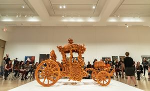 Photo of Dr. Emily Stamey talking with students about life-size carriage made of sugar