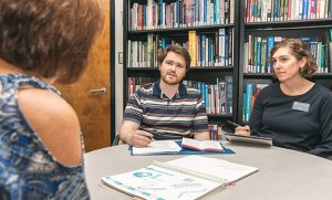 A male student and female faculty member sit at a table with a genetic counseling patient.