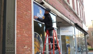 Photo of man installing signs in front of UNCG Pop up shop in downtown Greensboro.
