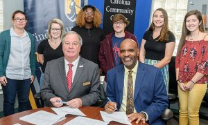 Photo of university leaders signing agreement with students standing behind them