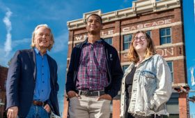 Three people stand with a downtown building