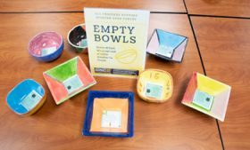 """Colorful bowls on a table with sign that says """"Empty Bowls"""""""