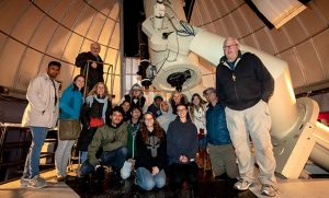 Group photo of students and faculty in front of telescope