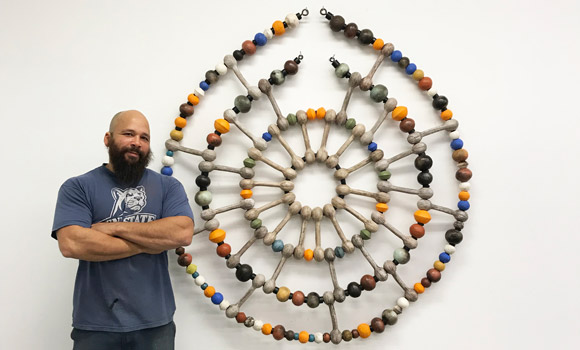 Alumnus and artist Sharif Bey standing beside his artwork, circular with earthen colors.