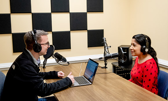 Photo of two people using podcasting equipment