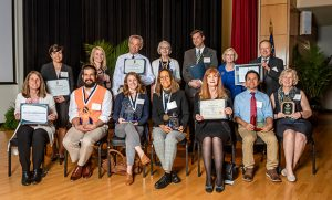 Group photo of faculty holding awards and certificates
