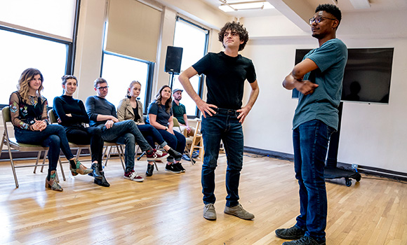 Photo of two students performing in front of group