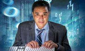 Professor Gupreet Dhillon with fingers on keyboard and math numbers behind him with blue background - like he's inside of a computer.