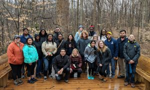Group photo of students and faculty in front of tree.