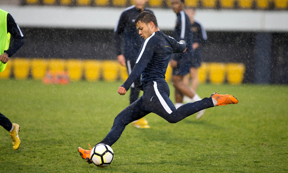 A soccer player about to kick the ball.