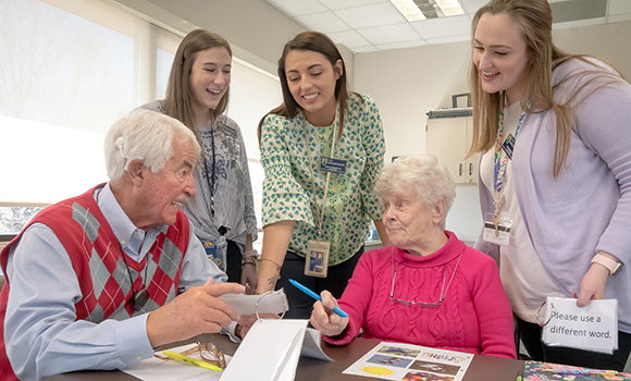 Photo of three graduate students with two older adults who have cochlear implants. They are sitting around a table, laughing and talking.