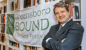 Dr. Martin Halbert in front of a banner for Greensboro Bound