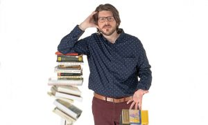 Photo of Matt Phillips leaning on a pile of books that is falling