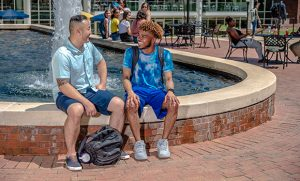 Photo of students talking at fountain on campus