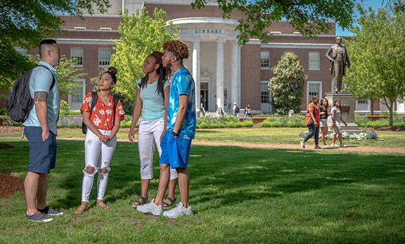 Photo of students on campus with library in background