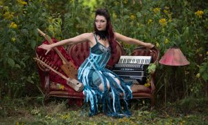 Photo of Crystal sitting on couch with musical instruments