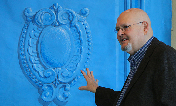 Photo of Joe Forbes in front of artwork