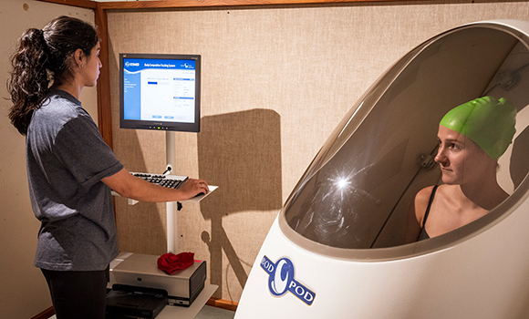 Photo of student conducting study with participant in bod pod