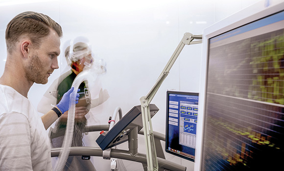 Photo of person running on treadmill while being hooked up to monitors and assessed by researcher