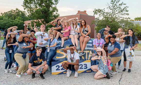 Group photo of SOAR students in front of rock on campus