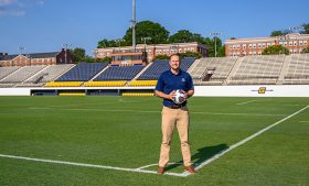 Chris Rich standing on soccer field with soccer ball in his hands