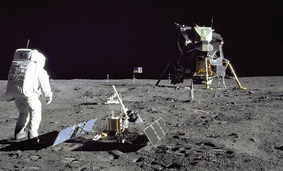 man walking on moon with craft in background