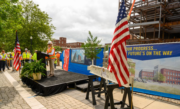 woman speaking at podium at construction site