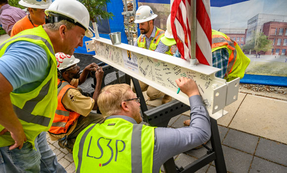 men in hard hats signing a steel beam