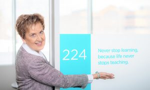 """Portrait of Joan Evans pointing to sign that says, """"Never stop learning, because life never stops teaching."""""""