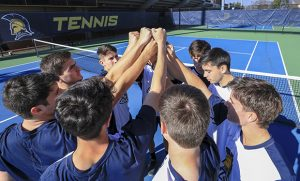 Photo of men's tennis team huddle on court