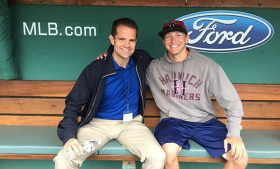 Two men pose for a photo in baseball dugout