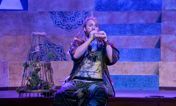 Performer plays flute on stage