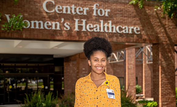 Photo of student in front of Center for Women's Healthcare