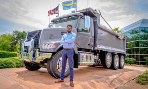 Photo of Dani Iqbal in front of large truck
