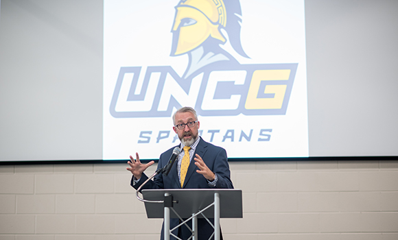 Photo of man talking at podium with UNCG logo in the background