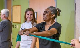 Graduate student smiles with a study participant pulling a resistance band