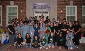 Students dressed as zombies and hospital personnel pose for a group photo in front of Foust Residence Hall
