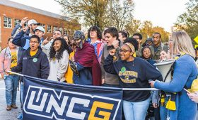 Students holding a UNCG banner and cheering while participating in Storm the Streets in 2018