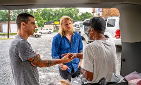 Photo of three men talking in parking lot
