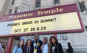 """students in front of the Masonic Temple in Detroit, Michigan under a marquee that reads: """"Forbes Under 30 Summit, October 27, 28, 29"""