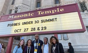 "students in front of the Masonic Temple in Detroit, Michigan under a marquee that reads: ""Forbes Under 30 Summit, October 27, 28, 29"