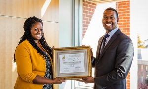 Ti'Era holding her certificate with Secretary of the N.C. Department of Environmental Quality Michael S. Regan