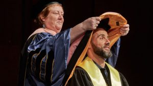 Dr. Kelly Burke confers a doctoral hood over the head of a graduate