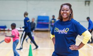 Photo of Trina Pratt in gym with kids playing in the background
