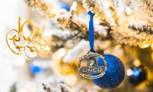 UNCG ornament hanging from a branch on a holiday tree.