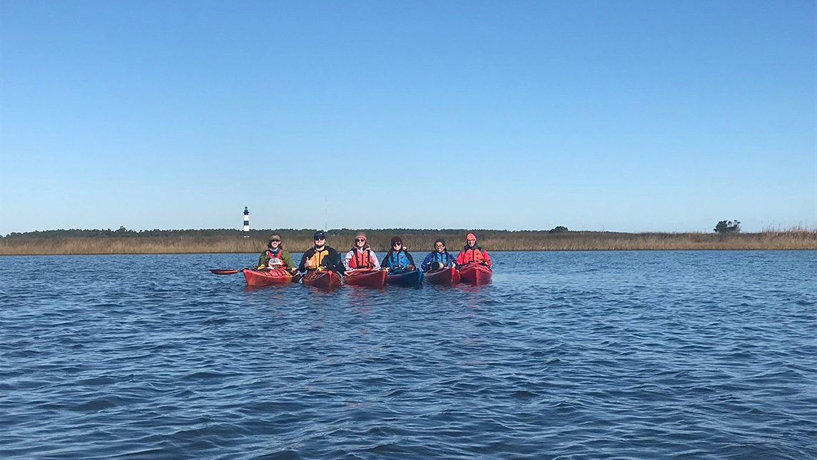 UNCG students kayaking on North Carolina shore.