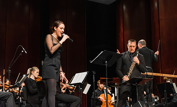 Becca Stevens singing into microphone, Chad Eby playing soprano saxophone, and an orchestra behind them on stage.