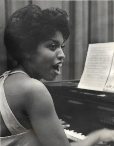 Photo of Baker playing piano